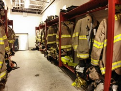 Pictures of fire gear hanging and firehose sitting at the ready.