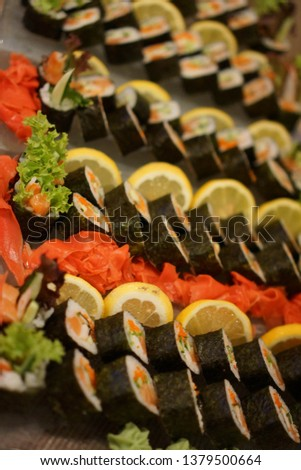 Pictures of fresh sushi dishes with a large variety decorated with lemon and colorful ginger with lettuce leaves. Selective focus on the beginning of the dish. Vertical frame.