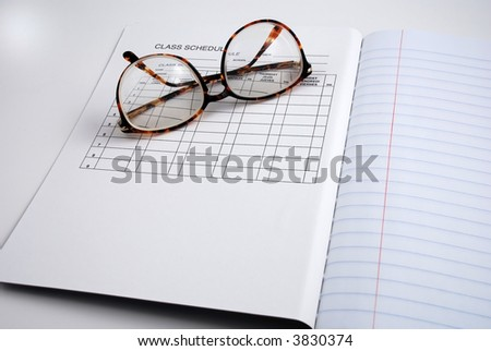Pictures of glasses resting on a blank notepad, ready to write and work