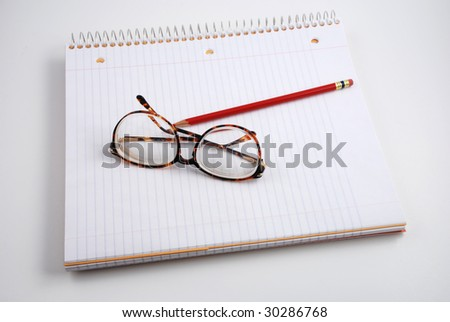 Pictures of glasses resting on a notepad, indicating the writer is taking a break from thinking - stock photo