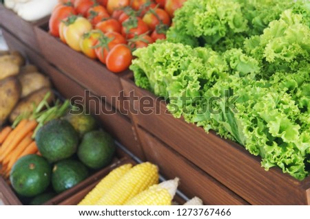 Pictures of various fruits placed in wooden crates such as tomatoes, corn, avocado, carrots, potatoes, cabbage and lettuce.