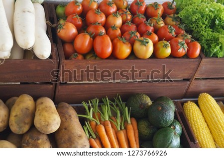 Pictures of various fruits placed in wooden crates such as tomatoes, corn, radish, avocado, carrots, potatoes, cabbage and lettuce.