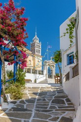 Picturesque alley in lefkes Paros greek island with a full blooming bougainvillea and  the cristian church of Agia Triada as background in the traditional village  lefkes Paros island, Greece