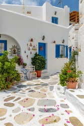 Picturesque alley in Prodromos Paros greek island with whitewashed traditional houses with blue door  and flowers all over !!!