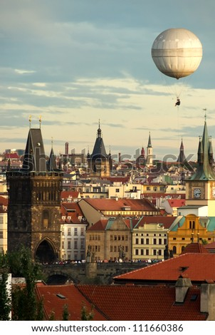 Picturesque and romantic view over the oldtown and the charles bridge of Prague having a balloon in the late afternoon sky. Soft colors.