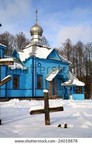 Picturesque blue Orthodox Church on a forest clearing, covered with the snow. Winter scenery. Important place of worship in small village Koterka, east part of Poland.