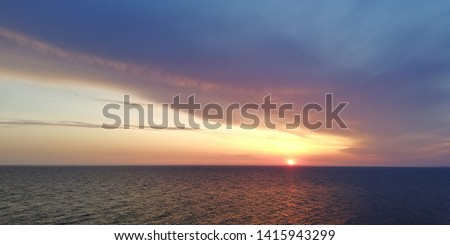 Picturesque bright background. Marine evening sunset landscape. Clouds podsvechenye setting sun, painted in red, pink, blue, purple colors.