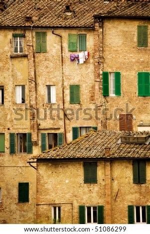 Picturesque building facades in  Siena Italy, with windows, shutters and tile roofs. - stock photo