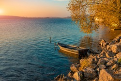 picturesque colorful autumn landscape calm water rocky coast line of country side lake with empty lonely wooden boat September yellow tree foliage and sunset orange sun light glare