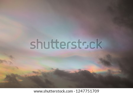 Picturesque dramatic colorful vibrant sky with clouds and rainbow. Tiny ice crystals or water droplets cause light to be diffracted – spread out – creating this rainbow-like effect in the clouds.