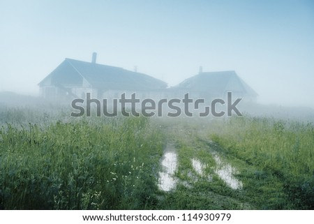 Picturesque farm ruins on hill in fog in morning. Road with puddles in deserted area in morning with fog
