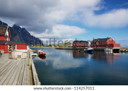 Picturesque fishing port in town of Henningsvaer on Lofoten islands in Norway with typical red wooden buildings and small fishing boats