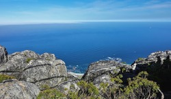 Picturesque gray spotted boulders against the backdrop of the blue Atlantic Ocean. A section of the coastline is visible. Fynbos bushes grow on the stones. Table Mountain top. Cape Town. South Africa