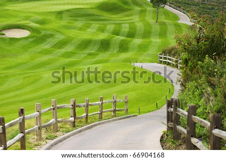 Picturesque green golf field with a wooden fence