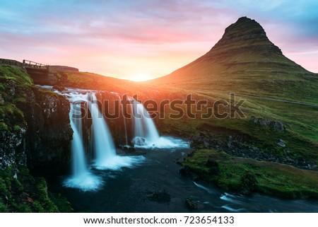 Picturesque icelandic landscape with colorful sunrise on Kirkjufellsfoss waterfall. Amazing morning scene near famous mountain - Kirkjufell volkano, Iceland, Europe #723654133
