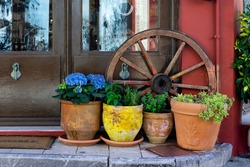 Picturesque icon from Archanes town in Heraklion prefecture Crete. Four flower pots with flowers and herbs and an old wooden carriage wheel behind them, in front of a local shop