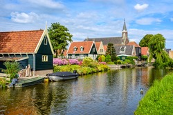 Picturesque idyllic De Rijp village in North Holland, Netherlands, view of characteristic wooden houses with red tiled roofs and flower beds and the church reflecting in a river