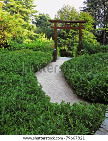 Picturesque Japanese park on the bank of the Italian lake. Wooden gate with traditional oriental symbols