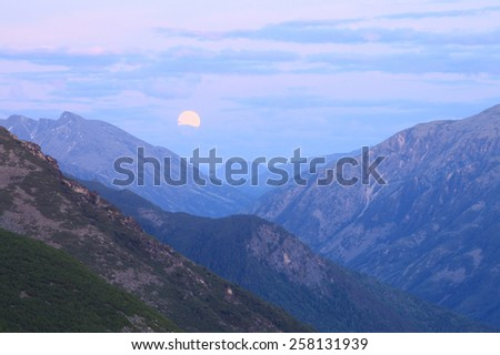 picturesque landscape moonrise in the Baikal Mountains during the night summer night