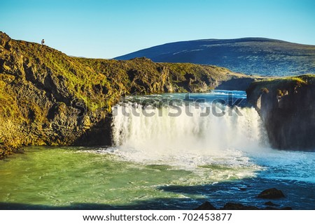 Picturesque landscape of a mountain waterfall and traditional nature of Iceland. #702453877