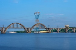 Picturesque landscape of the Ukrainian Dnipro city with old arch Railway Merefo-Kherson bridge across the Dniepr river in Ukraine.