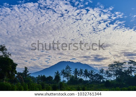 Picturesque landscape. Sunrise above Agung volcano, Bali island. Silhouette balinese sacred mountain Agung against the background of morning sky with a lot of clouds. Beauty world. Fantastic morning. #1032761344