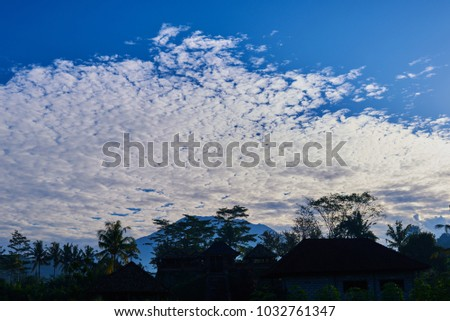 Picturesque landscape. Sunrise above Agung volcano, Bali island. Silhouette balinese sacred mountain Agung against the background of morning sky with a lot of clouds. Beauty world. Fantastic morning. #1032761347