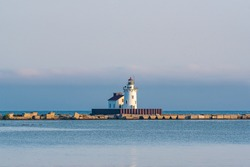 Picturesque lighthouse in bay with fog and calm water