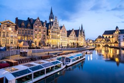 Picturesque medieval buildings on Leie river in Ghent town, Belgium at dusk.