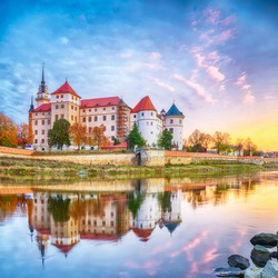 Picturesque morning view of Hartenfels castle on banks of the Elbe. Dramatic sunrise. Location: Torgau, NorthWestern Saxony, Germany, Europe