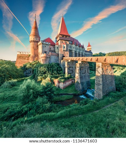 Picturesque morning view of Hunyad Castle / Corvin's Castle. Unbelievable summer sunrise in Hunedoara, Transylvania, Romania, Europe. Romanian castle landmarks. Traveling concept background.