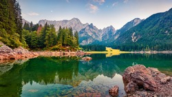 Picturesque morning view of Julian Alps. Splendid sunrise on Fusine lake. Majestic outdoor scene with Mangart peak on background, Province of Udine, Italy. Beauty of nature concept background.