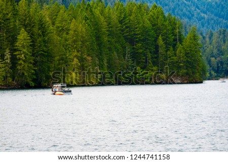 Picturesque mountain clear water deep Merwin Lake with evergreen coniferous forests on the mountains and the curvy shore and a floating boat with tourists– best place to healthy rest
