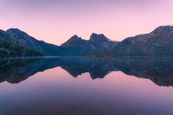 Picturesque nature background with Cradle Mountain and lake at sunrise with colorful sky and water reflection. Sunrise mountain background