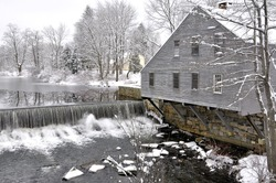 Picturesque New England winter scene. Squannacook River dam that once supplied power for this historic sawmill and cooperage in Townsend, Massachusetts.