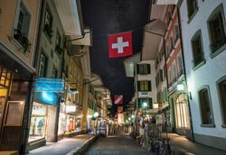 Picturesque nightscape of illuminated Upper Main street (Obere Hauptgasse) of Thun, Switzerland under starry sky. Thun city is a popular travel destination and tourist attraction in Switzerland