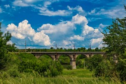 Picturesque old arched railway bridge across the river Sluch on the background of a cloudy sky at bright summer day. Ukraine