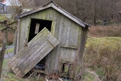 Picturesque old dilapidated chicken shed, with door hanging off, in rural setting in Wales