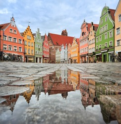Picturesque old gothic houses reflecting in a puddle in a german city near Munich