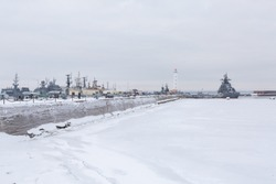 Picturesque panorama of dock with military ships and a lighthouse in Russia.