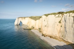 Picturesque panoramic aerial view of the Etretat white cliffs at sunset. Dramatic sky, azure water. Summer vacations in Normandy, France. Travel destinations, national landmark, sightseeing, history