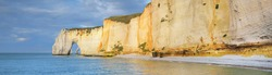 Picturesque panoramic view of the Etretat white cliffs at sunset. Cloudy blue sky, azure water. Summer vacations in Normandy, France. Travel destinations, national landmark, sightseeing, history