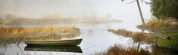 Picturesque panoramic view of the forest river in a thick fog. Mossy tree trunks and plants, old fishing boat close-up. Misty autumn landscape. Dark fairytale. Ecology, ecosystems
