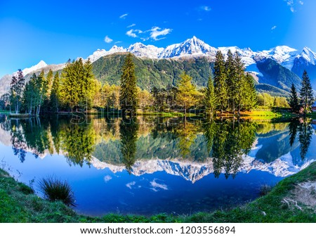 Picturesque park in the mountain resort of Chamonix, at the foot of Mont Blanc. Snowy peaks of the Alps are beautifully reflected in the lake. Concept of active and ecotourism #1203556894