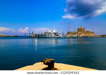 Picturesque port on the sea - dock, white ship, medieval fortress, turquoise and blue water. Rhodes, Greece - - the best Island for excursions, travel, recreation and vacation.\n