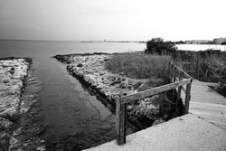 Picturesque rocky beach in Italy. Black and white photo shows a wooden bridge.