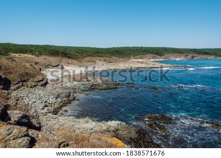 Picturesque rocky coastline with separate small sandy beaches separated by rocks that cut into the blue sea in the background a dense green forest and clear blue sky. Zdjęcia stock ©