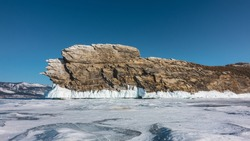 Picturesque rocky island on a frozen lake. Bizarre outlines of the cliff, cracks in the stones, ice splashes on the base, icicles. Snow on ice. The background is clear blue sky. Baikal