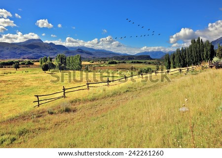 Picturesque rural landscape. Light wood fences are installed on the slopes of the hilly land