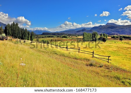 Picturesque rural landscape. Light wood fences are installed on the slopes of the hilly land. South America, Chile